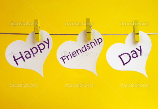 Celebrate International Friendship Day with Happy Friendship Day message across three white heart tags hanging from pegs on a line against a yellow background.
