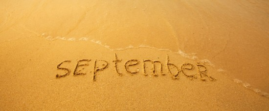September - written in sand on beach texture - soft wave of the sea (months year series)