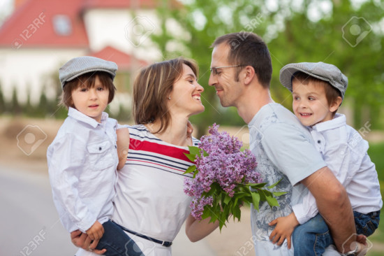 Family of four, mother, father and two boys, parent having the kids on piggy back, laughing, smiling, hugging, giving a kiss, holding flowers